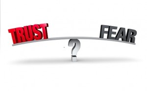 "A red ""TRUST"" and a gray ""FEAR"" sit on opposite ends of a gray board which is balanced on a white question mark. Isolated on white."